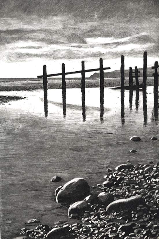 STICKS AND STONES - Low tide at Winchelsea beach near Rye, the weather-beaten groynes stand in silhouette against the headland at Fairlight, East Sussex.